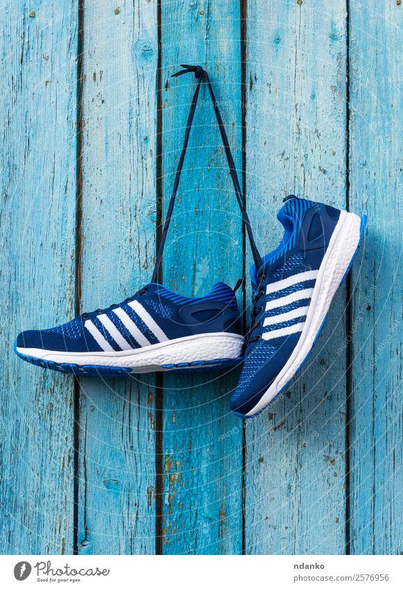 männliche blaue Textilsneakers Lifestyle Sport Mode Bekleidung Schuhe Turnschuh Holz alt Fitness hängen Hintergrund Paar nageln Sporthalle rennen Wand erhängen
