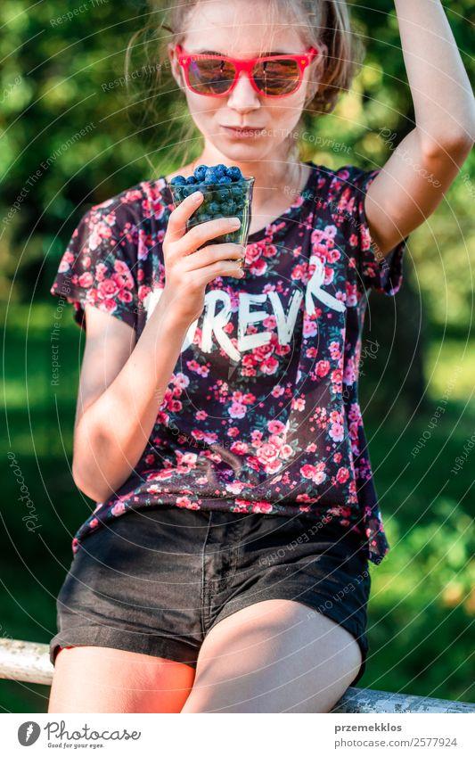 Glückliches Mädchen, das es genießt, die frischen Heidelbeeren im Freien zu essen. Lebensmittel Frucht Dessert Ernährung Essen Vegetarische Ernährung Diät Glas