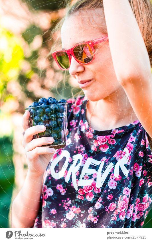 Glückliches Mädchen genießt das Essen der frischen Heidelbeeren. Lebensmittel Frucht Ernährung Vegetarische Ernährung Diät Glas Lifestyle Sommer Mensch