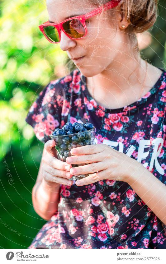 Glückliches Mädchen genießt das Essen der frischen Heidelbeeren. Lebensmittel Frucht Ernährung Vegetarische Ernährung Diät Glas Lifestyle Sommer Garten Mensch