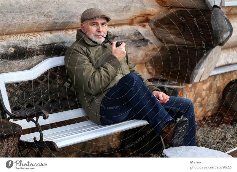 Der Mann raucht eine Pfeife sitzen Bank Rauchen Tabakwaren Haus kalt Winter Holz Bart Erwachsene Mensch