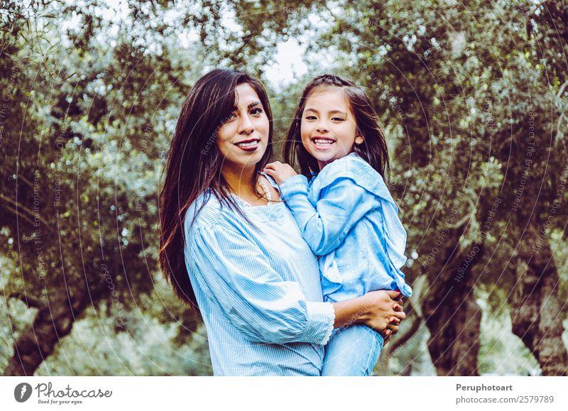 Mutter trägt ihre süße und lächelnde Tochter im Park. Mensch Kind Baby Mädchen Junge Frau Jugendliche Erwachsene Eltern Familie & Verwandtschaft Freundschaft