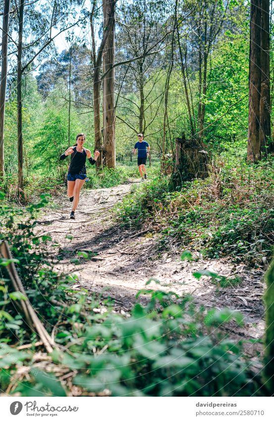 Junge Frau und Mann auf Spurensuche Lifestyle Abenteuer Sport Mensch Erwachsene Paar Natur Baum Wald Wege & Pfade Fitness authentisch Geschwindigkeit anstrengen