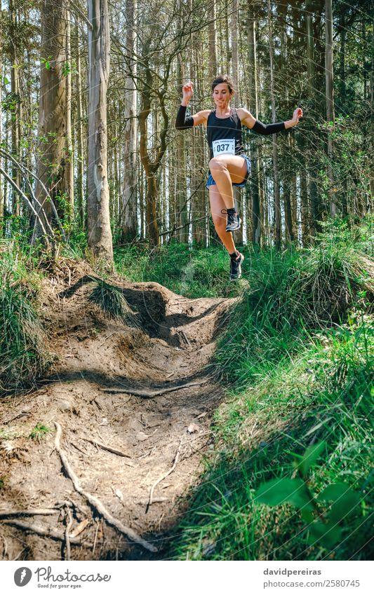 Springende Frau, die am Trail Race teilnimmt. Lifestyle Sport Mensch Erwachsene Natur Baum Wald Wege & Pfade Fitness springen authentisch Geschwindigkeit