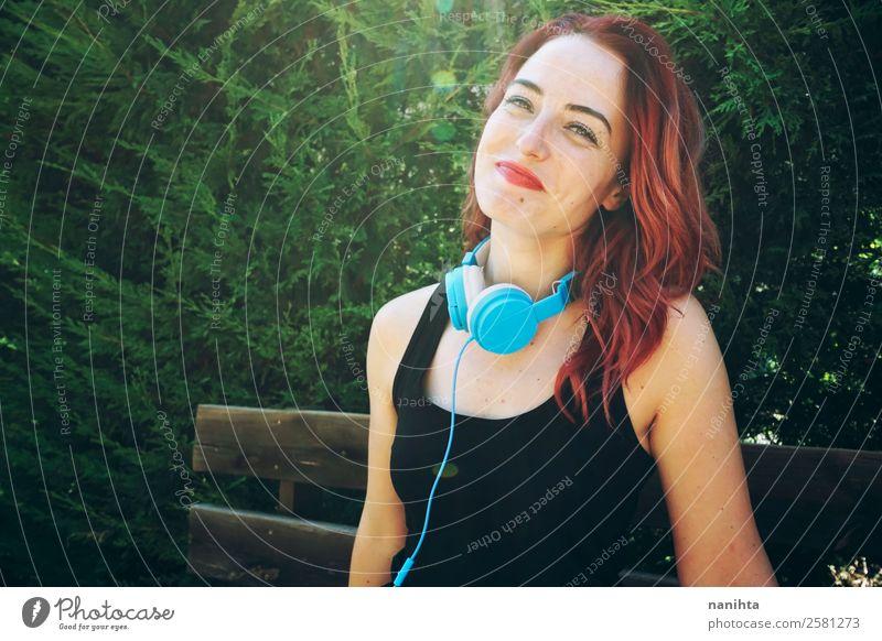 Smiley sportliche Frau in einem Park Lifestyle Stil Freude Haare & Frisuren Gesundheit Wellness Wohlgefühl Freizeit & Hobby Headset Kopfhörer