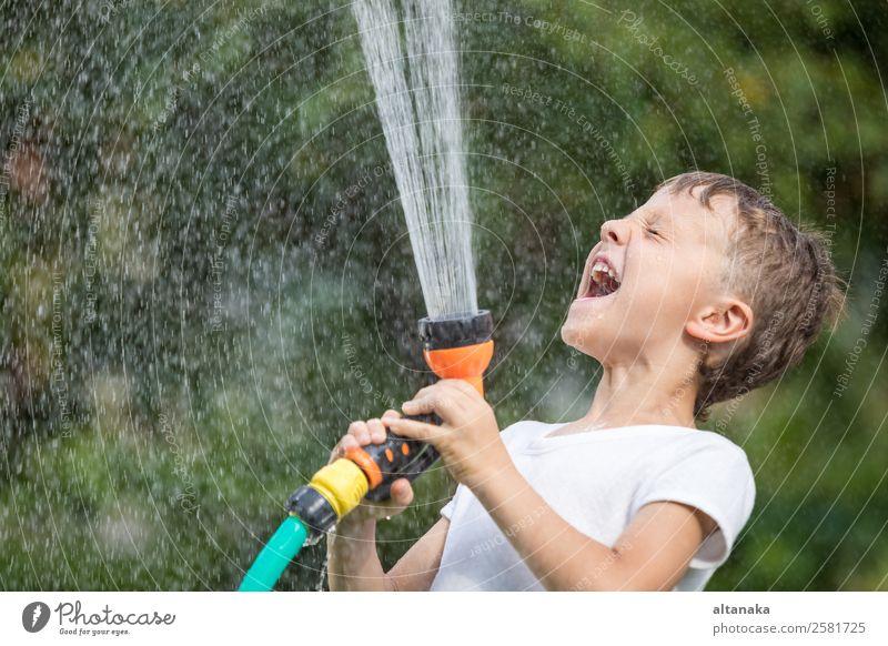 Glücklicher kleiner Junge, der Wasser aus einem Schlauch gießt. Kind hat Spaß im Freien. Freude Freizeit & Hobby Spielen Ferien & Urlaub & Reisen Freiheit