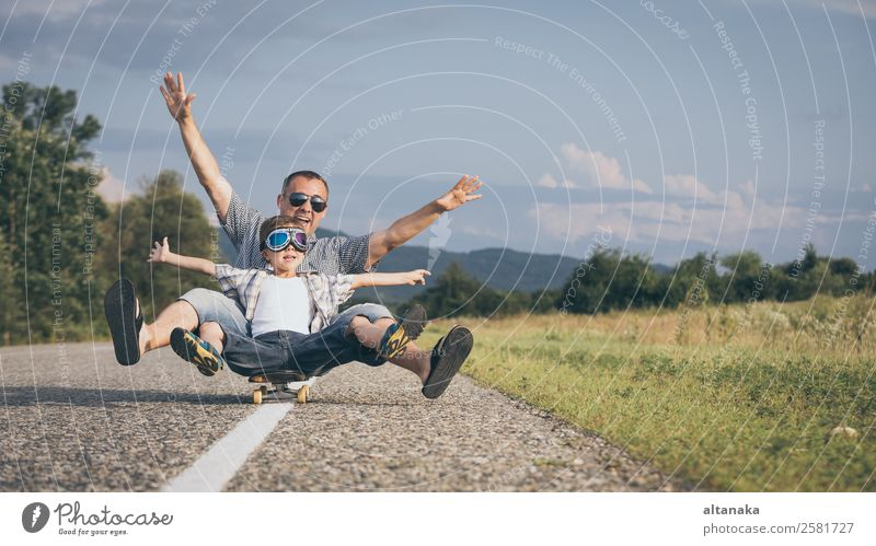 Vater und Sohn spielen zur Tageszeit auf der Straße. Die Menschen haben Spaß im Freien. Konzept der freundlichen Familie. Lifestyle Freude Glück
