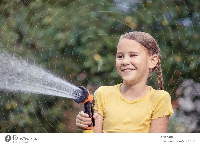 Glückliches kleines Mädchen, das Wasser aus einem Schlauch gießt. Freude Freizeit & Hobby Spielen Ferien & Urlaub & Reisen Freiheit Camping Sommer Haus Garten