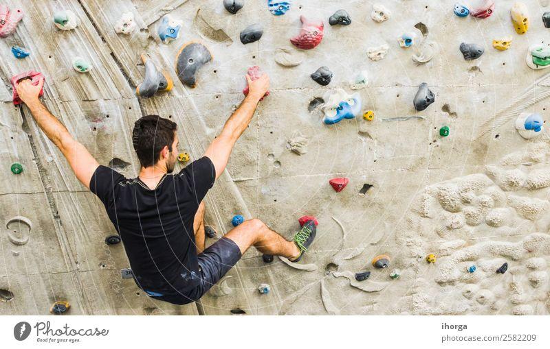 Ein Mann übt das Klettern an einer künstlichen Wand in Innenräumen. Lifestyle Freude Freizeit & Hobby Sport Bergsteigen Junger Mann Jugendliche Erwachsene 1
