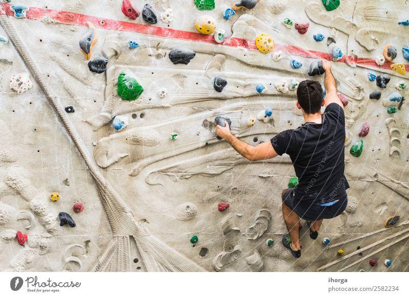 Ein Mann übt das Klettern an einer künstlichen Wand in Innenräumen. Lifestyle Freude Freizeit & Hobby Sport Bergsteigen Erwachsene Hand Finger Fuß 1 Mensch