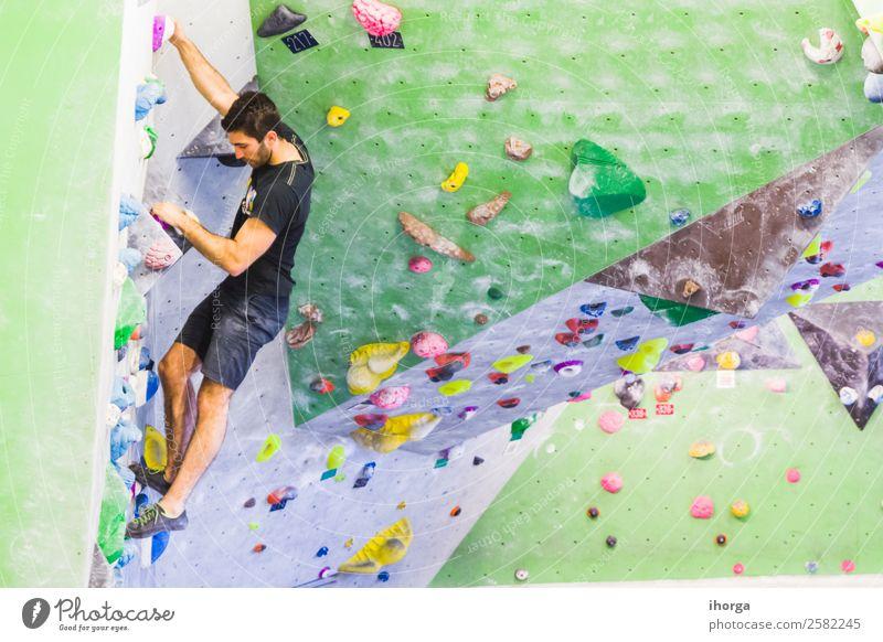 Ein Mann übt das Klettern an einer künstlichen Wand in Innenräumen. Lifestyle Freude Freizeit & Hobby Sport Bergsteigen Junger Mann Jugendliche Erwachsene Hand