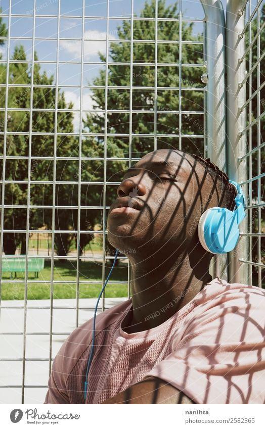 Junger Mann genießt Sonne und Musik Lifestyle Stil Design Sinnesorgane Erholung Meditation Freizeit & Hobby Headset Kopfhörer Technik & Technologie