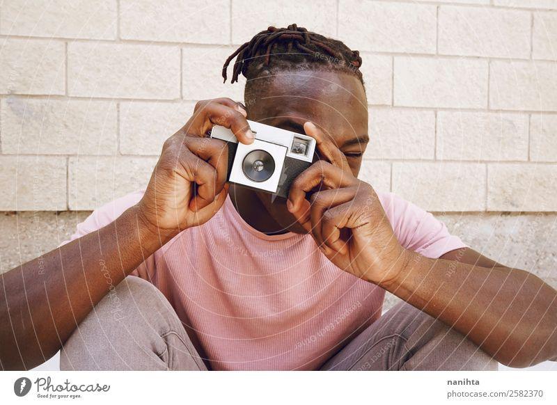 Junger Mann, der mit einer Kamera fotografiert. Lifestyle Stil Design Freizeit & Hobby Arbeit & Erwerbstätigkeit Beruf Fotokamera Technik & Technologie