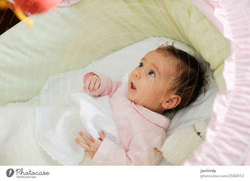 Babymädchen zwei Monate alt, das eine Puppe in seiner Krippe ansieht. Freude Glück schön Gesicht Leben Kind Fotokamera Mensch Mädchen Kindheit 1 0-12 Monate