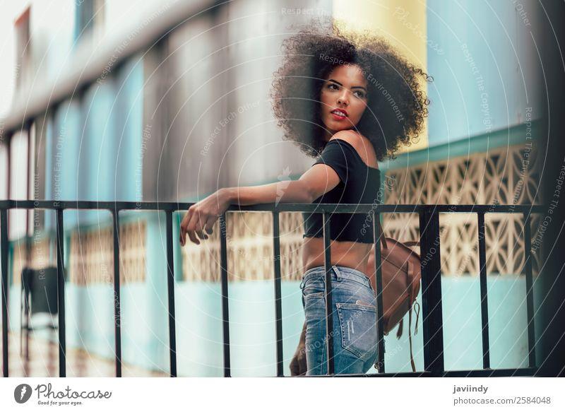 Junge gemischte Frau mit Afrohaar, die auf der Straße steht. Lifestyle Stil schön Haare & Frisuren Gesicht Mensch feminin Junge Frau Jugendliche Erwachsene 1