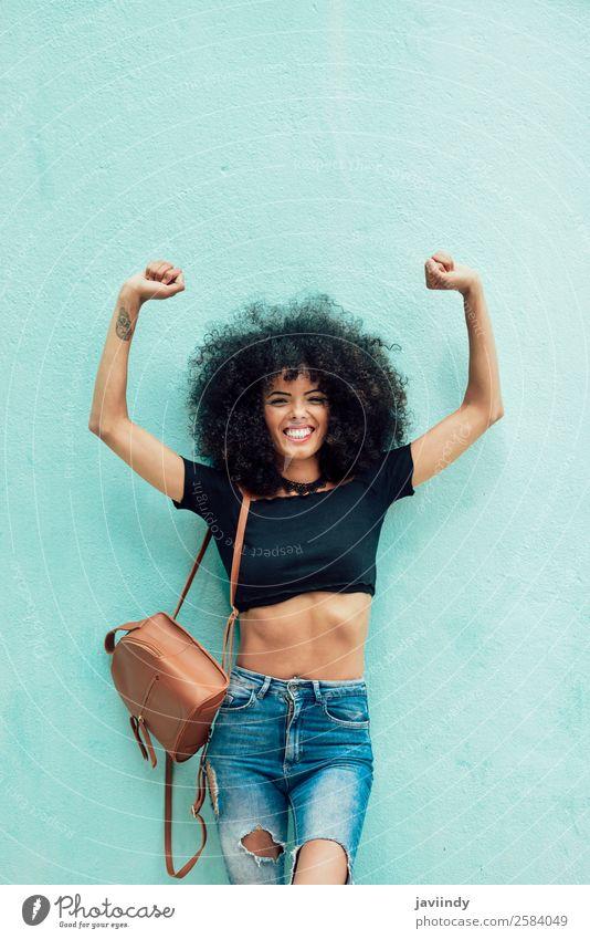 Lustige schwarze Frau mit Afrohaar, die die Arme im Freien hebt. Lifestyle Stil Freude Glück schön Haare & Frisuren Gesicht Mensch feminin Junge Frau