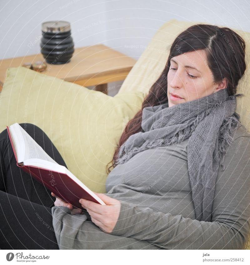 schmökern Wohnung Sofa Raum Wohnzimmer Mensch feminin Frau Erwachsene 1 30-45 Jahre brünett langhaarig Buch lesen sitzen Farbfoto Innenaufnahme Tag