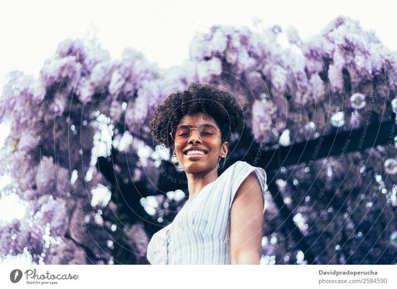 Fröhliche junge schwarze Frau, umgeben von Blumen. Lifestyle Glück schön Erholung Sommer Garten Erwachsene Natur Baum Blüte Kleid Sonnenbrille Lächeln