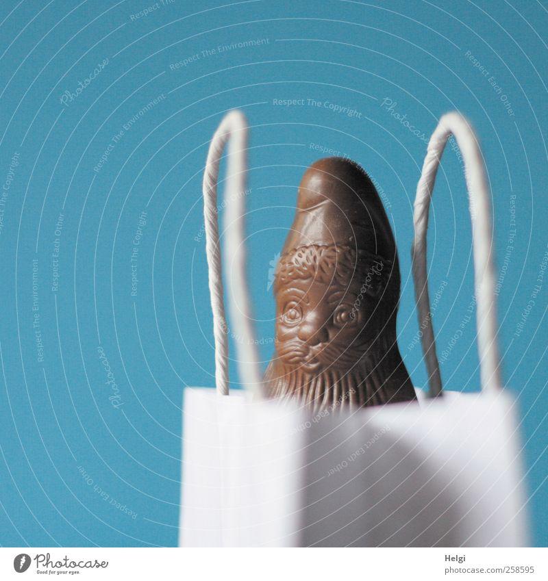 Schokoladenweihnachtsmann schaut aus einer weißen Papiertüte vor blauem Hintergrund Süßwaren Weihnachtsmann Verpackung Tüte Tasche Tragegriff kaufen stehen