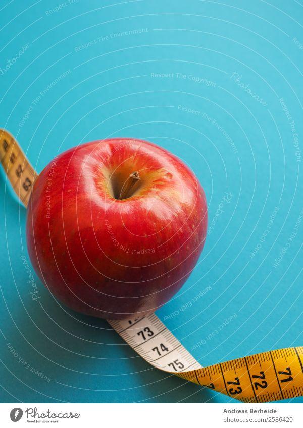 Roter Apfel mit einem Maßband Frucht Bioprodukte Vegetarische Ernährung Diät Fasten Lifestyle Gesunde Ernährung Übergewicht Leben Wohlgefühl