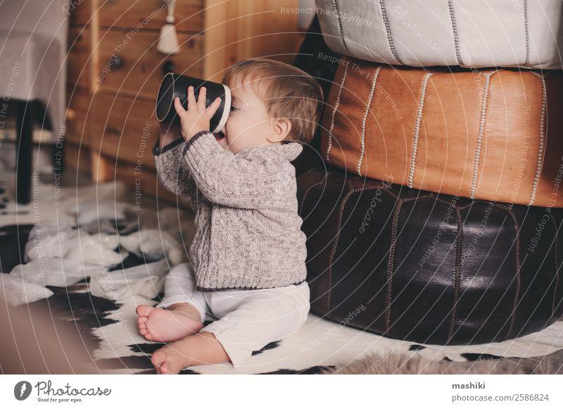 süßer kleiner Junge, der zu Hause mit dem Becher spielt. Tee Lifestyle Stil Glück Spielen Winter Schlafzimmer Kind Baby Kindheit Wärme Pullover sitzen modern