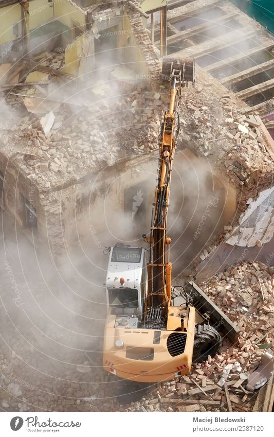 Gebäudeabbruch mit einem Bagger in der Staubwolke. Haus Baustelle Maschine Ruine Arbeit & Erwerbstätigkeit Tod Überleben Verfall Vergangenheit verlieren