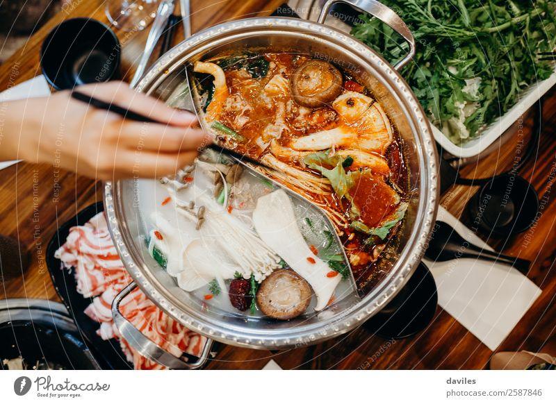 Koreanisches Eintopfgericht, von oben betrachtet, und eine Hand nimmt mit Stäbchen Essen daraus. Lebensmittel Fleisch Gemüse Suppe schmoren Abendessen
