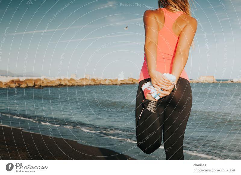 Sportlerin, die am Strand die Beine streckt, mit dem Meer im Hintergrund. Lifestyle Körper Sommer Fitness Sport-Training Joggen Mensch feminin Junge Frau