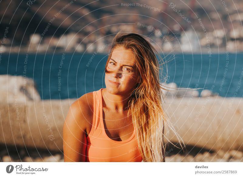Schöne Frau in Sportkleidung, die bei Sonnenuntergang auf einer Betonmauer im Freien sitzt. Lifestyle schön Körper Freizeit & Hobby Meer Fitness Sport-Training