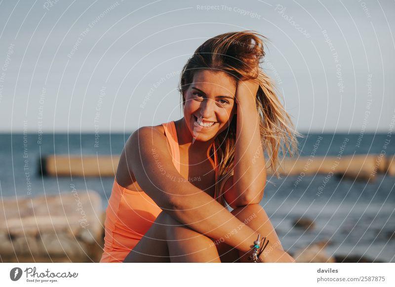 Schöne Frau in Sportkleidung, die bei Sonnenuntergang auf einer Betonmauer im Freien sitzt. Lifestyle Freude schön Körper Wellness Erholung Meer Fitness
