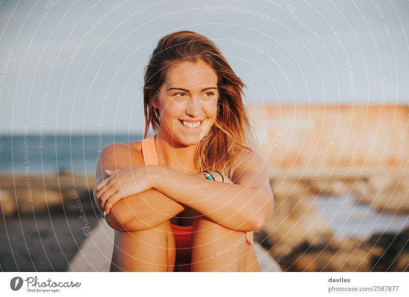 Schöne Frau in Sportkleidung, die bei Sonnenuntergang auf einer Betonmauer im Freien sitzt. Lifestyle Freude schön Körper Wellness Erholung Freizeit & Hobby