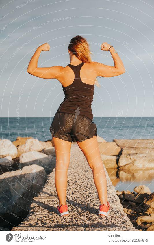 Junges Mädchen mit starkem Bizeps nach Fitnesstraining im Freien. Fitness-Frau. Ganzkörper-Rückenansicht. Freude Glück schön Körper Sommer Strand Sport Erfolg