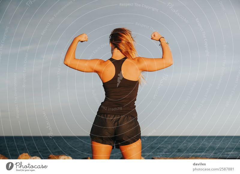 Junges Mädchen mit starkem Bizeps nach Fitnesstraining im Freien. Fitness-Frau. Ganzkörper-Rückenansicht. Freude schön Körper sportlich Sommer Strand Sport