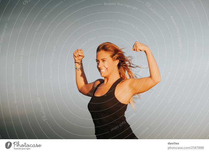 Lächelnde Frau mit starkem Bizeps nach Fitnesstraining im Freien. Fitness-Mädchen. Freude schön Körper Wohlgefühl Sommer Sport Leichtathletik Erfolg Mensch