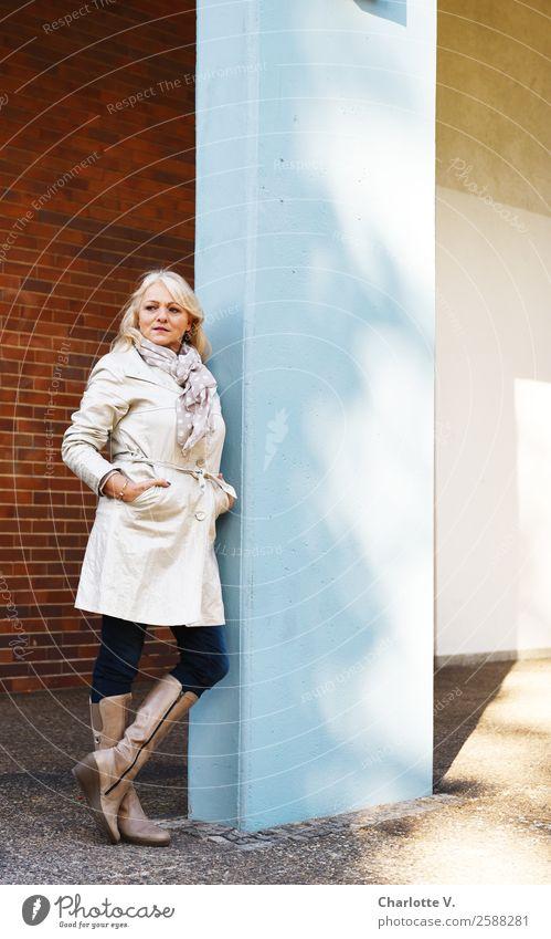Selbstbewusst Stil Mensch feminin Frau Erwachsene Weiblicher Senior 1 45-60 Jahre Mauer Wand Säule Mantel Trenchcoat Stiefel blond langhaarig Beton leuchten