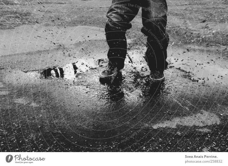 . Junge Beine Fuß 1 Mensch 3-8 Jahre Kind Kindheit Straße Teer Asphalt Jeanshose Schuhe Chucks Bewegung springen dreckig nass Lebensfreude Schwarzweißfoto