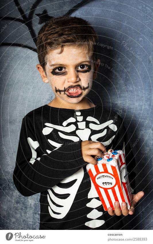 Kleines Kind in einem Skelettkostüm isst an Halloween gefälschte Augen. Freude Glück Gesicht Schminke Feste & Feiern Karneval Jahrmarkt Mensch Kleinkind Junge