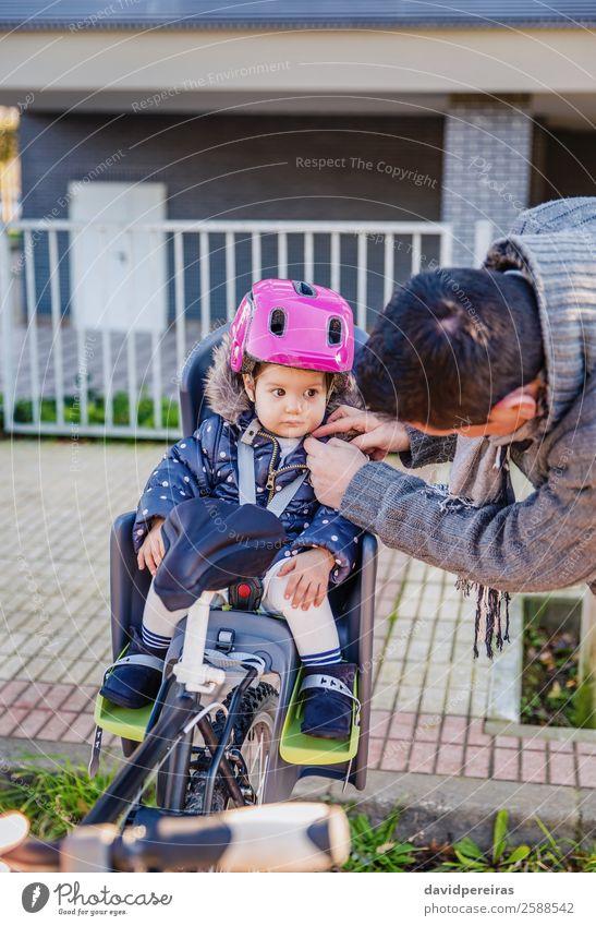 Vater schließt Helm zu ihrer Tochter, die im Fahrradsattel sitzt. Lifestyle Freizeit & Hobby Ferien & Urlaub & Reisen Ausflug Stuhl Fahrradfahren Kind Baby