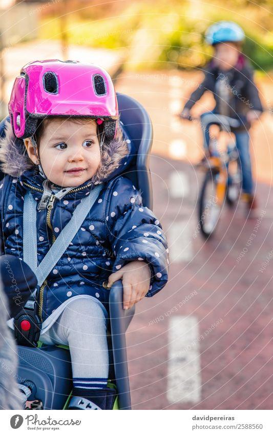 Kleines Mädchen mit Helm auf dem Kopf im Fahrradsattel sitzend Lifestyle Freizeit & Hobby Ferien & Urlaub & Reisen Ausflug Winter Stuhl Kind Baby Kleinkind Frau