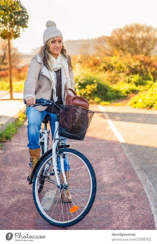 Junge Frau sitzt über dem Fahrrad auf einem Straßenradweg. Lifestyle Glück schön Erholung Freizeit & Hobby Sonne Winter Sport Fahrradfahren Mensch Erwachsene