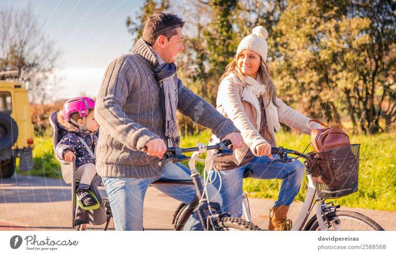 Familie mit kleiner Tochter, die auf einem Fahrradsattel sitzt und Fahrräder fährt. Lifestyle Glück Erholung Freizeit & Hobby Ferien & Urlaub & Reisen Sonne