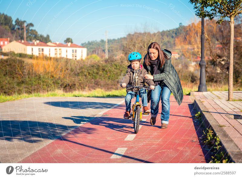 Mutter bringt ihrem Sohn bei, Fahrrad zu fahren. Lifestyle Freude Glück Freizeit & Hobby Spielen Sonne Winter Sport Erfolg Fahrradfahren Kind Schule Junge Frau