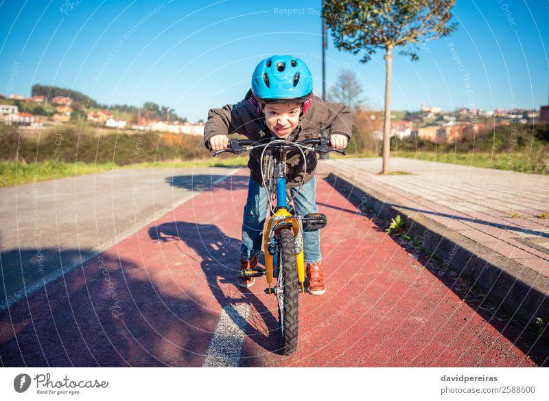 Porträt eines Jungen mit trotziger Geste über seinem Fahrrad, bereit zum Laufen. Lifestyle Freude Glück Gesicht Freizeit & Hobby Spielen Sonne Winter Sport