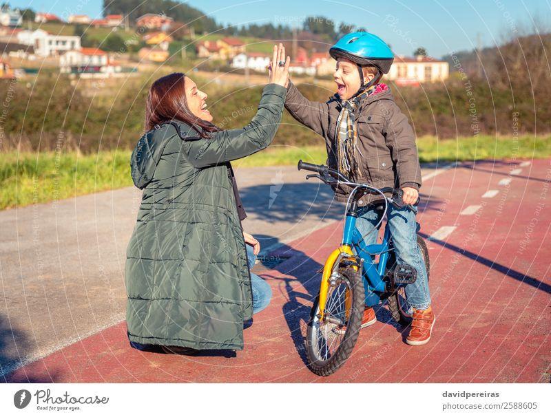 Mutter und Sohn, die fünf Personen geben, lernen Fahrrad zu fahren. Lifestyle Freude Glück Freizeit & Hobby Spielen Sonne Winter Sport Erfolg Fahrradfahren Kind