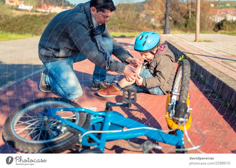 Vater legt dem Sohn ein Gipsband über die Knieverletzung. Medikament Sport Fahrradfahren Kind Junge Mann Erwachsene Band Straße Wege & Pfade schreien
