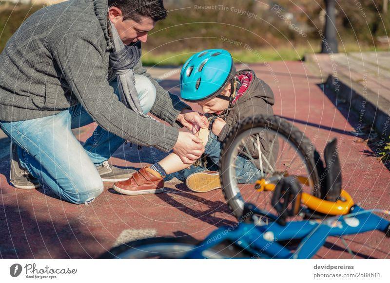 Vater legt Gipsband über Knieverletzung bei seinem Sohn. Medikament Sport Kind Junge Mann Erwachsene Straße Wege & Pfade schreien Traurigkeit weinen Schutz