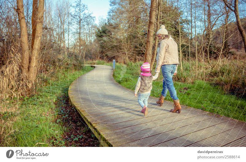 Rückansicht von Mutter und Tochter, die über einen Holzweg gehen. Lifestyle Freude Glück ruhig Freizeit & Hobby Freiheit Winter Kind Frau Erwachsene Eltern
