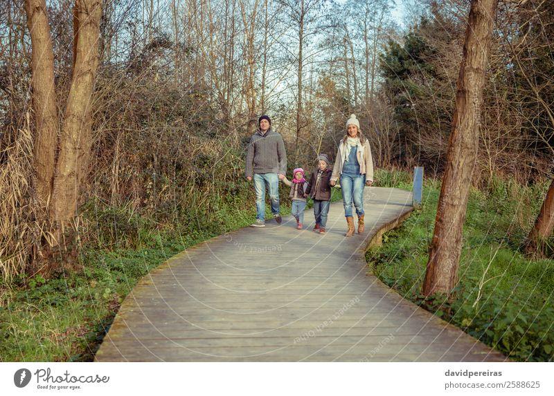 Glückliche Familie, die gemeinsam im Wald Hand in Hand geht. Lifestyle schön Freizeit & Hobby Ferien & Urlaub & Reisen Winter Kind Mensch Junge Frau Erwachsene