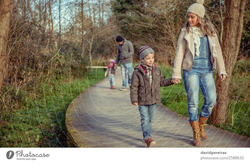 Glückliche Familie, die gemeinsam im Wald Hand in Hand geht. Lifestyle schön Winter Kind sprechen Mensch Junge Frau Erwachsene Mann Eltern Mutter Vater