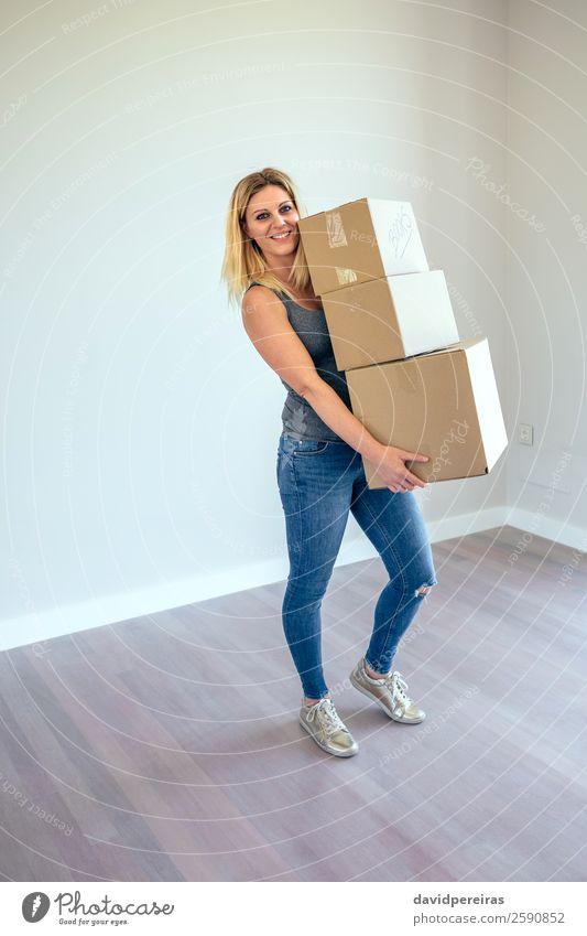 Frau mit Umzugskisten Glück schön Haus Umzug (Wohnungswechsel) Wohnzimmer Mensch Erwachsene Buch Jeanshose Turnschuh blond Kasten Lächeln stehen tragen
